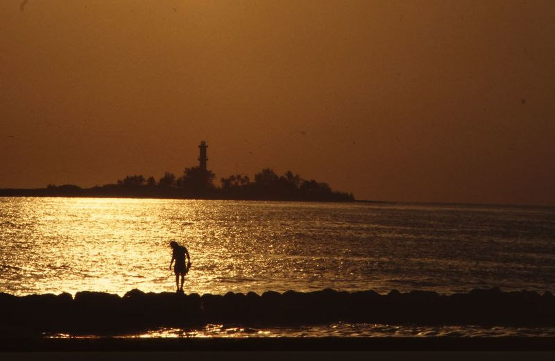 Silhouette man standing by sea against orange sky