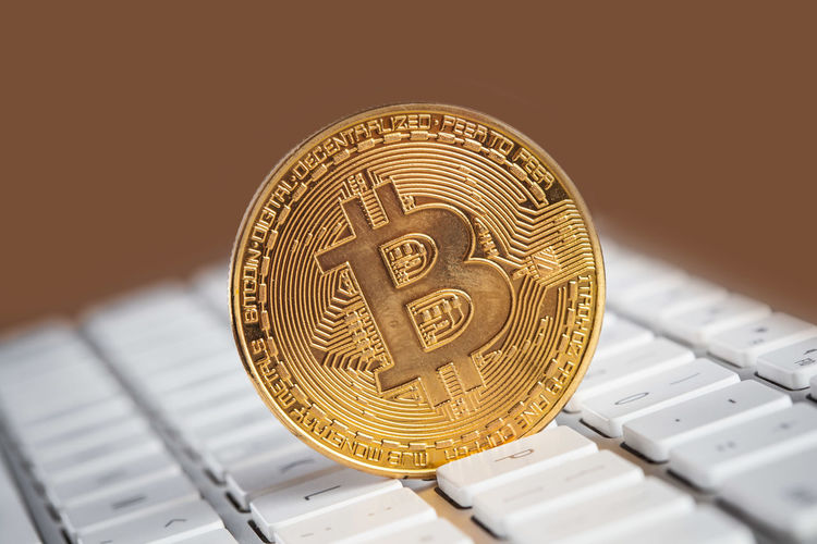Golden Bitcoin standing upright on white keyboard with copy space Currency Golden Bitcoin Close-up Coin Computer Keyboard Concept Concert Connection Cryptocurrency Day Finance Glowing Gold Gold Colored Indoors  Keyboard Network No People Online  Technology