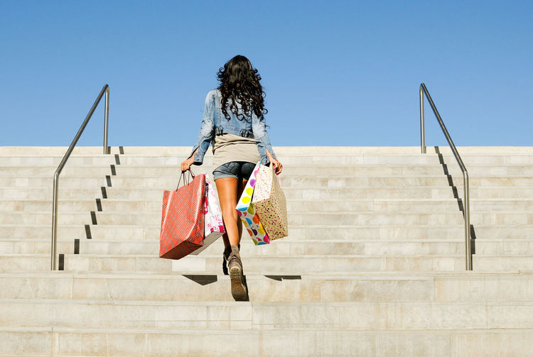 Low angle view of mid adult woman with shopping bags moving up on steps against clear blue sky