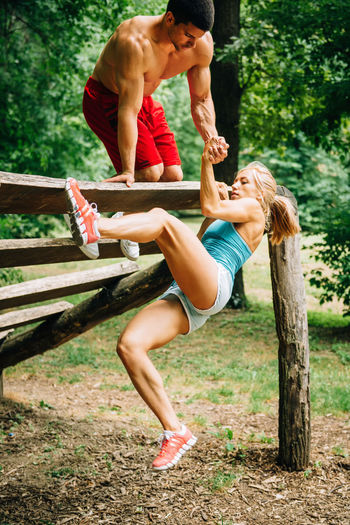 Full Length Of Woman Exercising With Man On Field