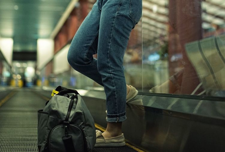 Low section of man walking on airport