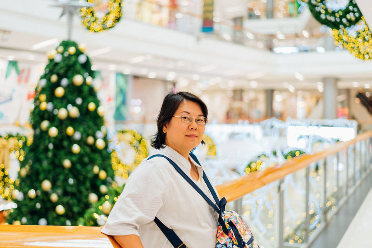 Portrait of smiling woman standing in mall