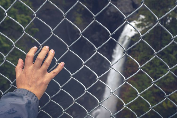 Cropped hand of person on fence against waterfall