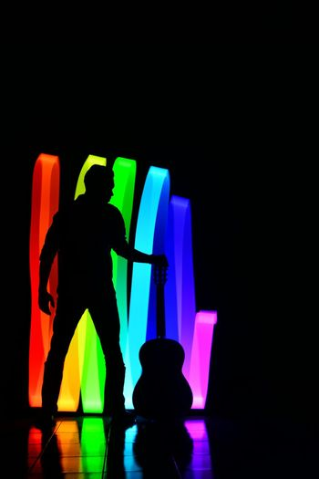 Silhouette man with multi colored lights
