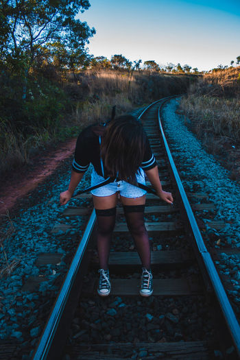 Full length of woman standing on railroad tracks during sunset