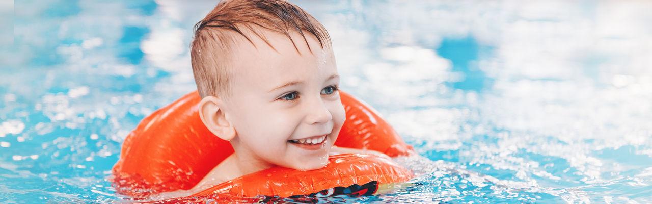 Smiling cute boy in swimming pool