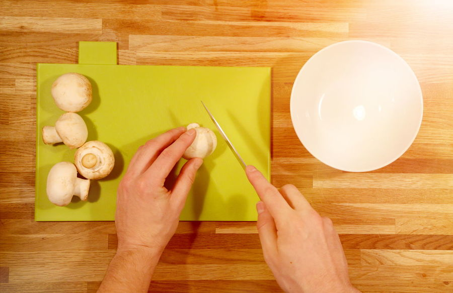 Cutting mushrooms Adult Close-up Cutting Cutting Board Day Food Food And Drink Freshness Hands Healthy Eating Healthy Lifestyle Holding Human Body Part Human Hand Indoors  Knife Lifestyles Mushroom One Person People Real People Table Wood Wood - Material