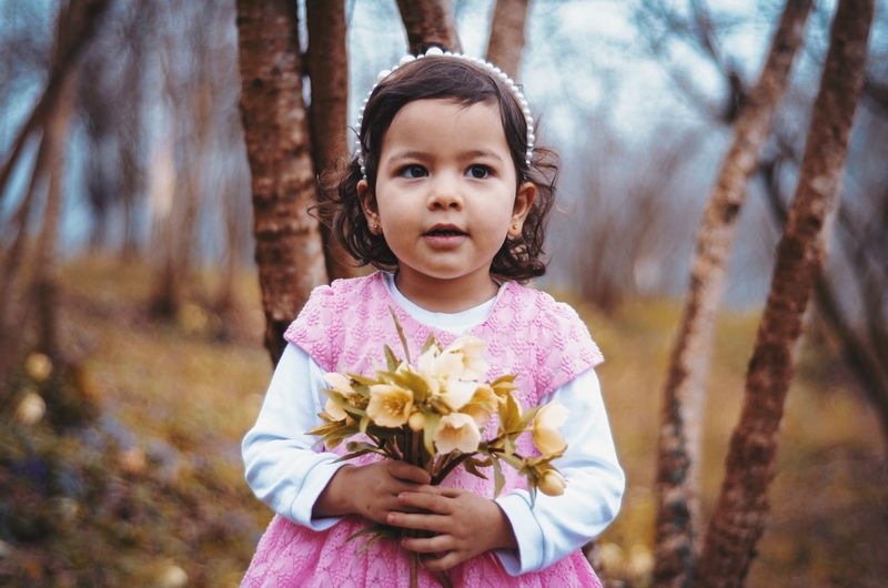 Innocent girl holding flowers on field
