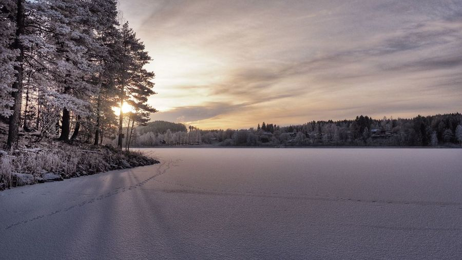 Scenic view of frozen lake against cloudy sky at sunset