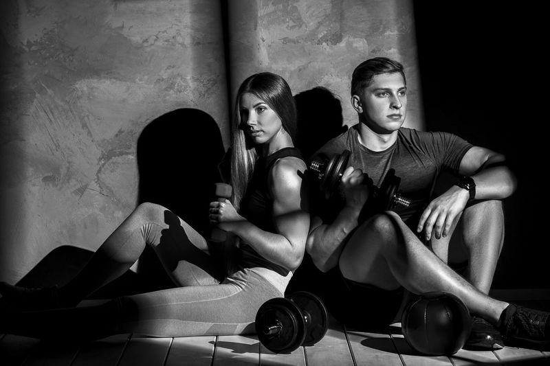 Instructor and woman holding dumbbell while sitting on floor