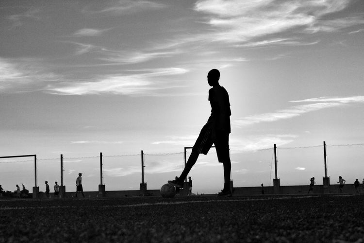 Silhouette boy holding ball under foot