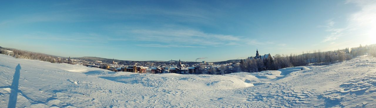 Panoramic shot of snow covered landscape against sky