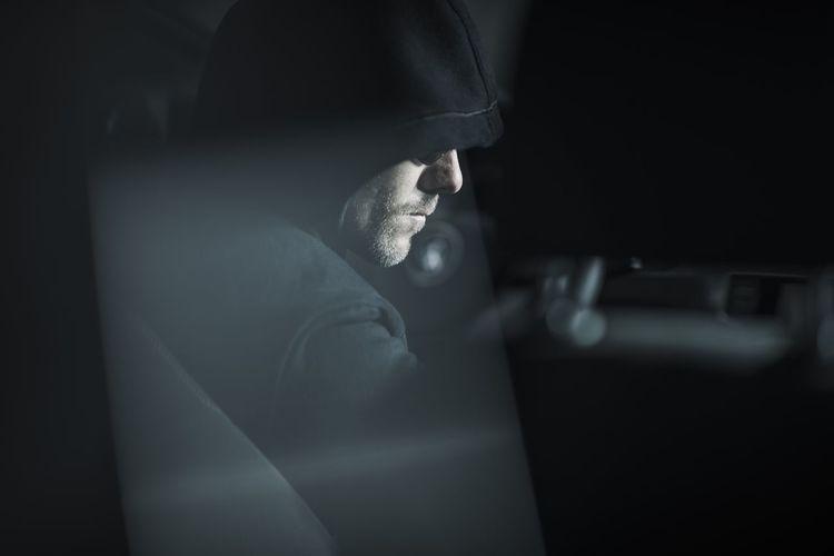 Side view of serious burglar stealing car