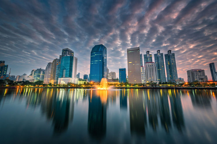 Reflection of illuminated buildings in city against sky during sunset