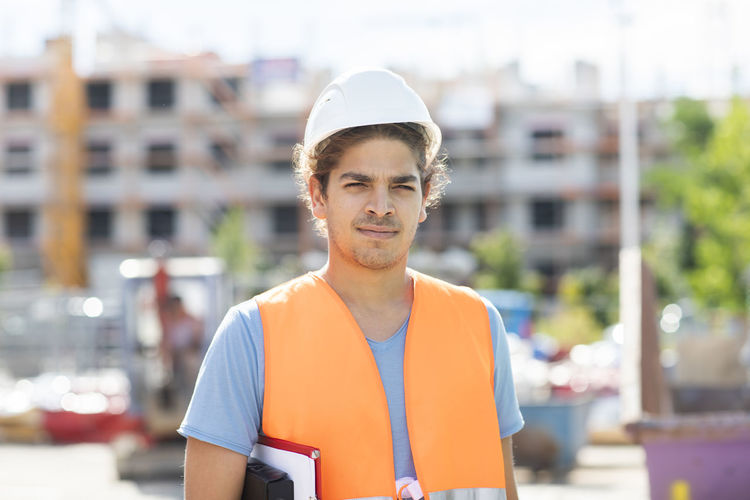Portrait of young man against construction site in city