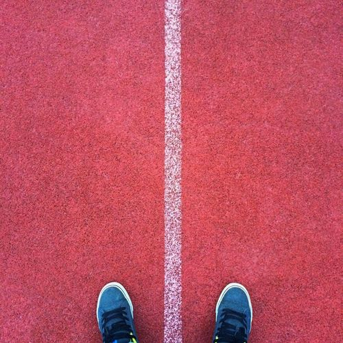 Low section of person standing on running track