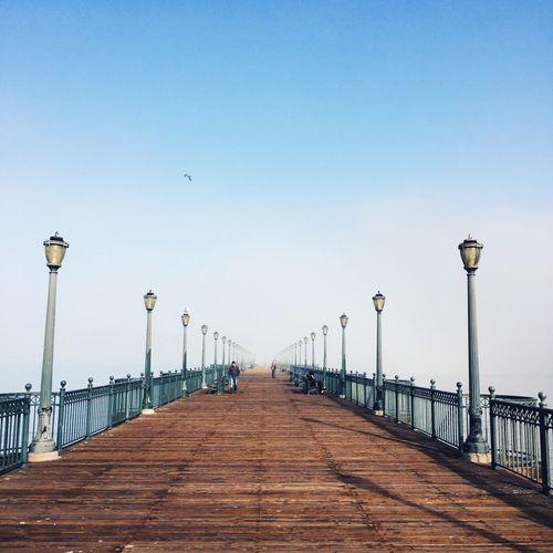Street lights on bridge against clear blue sky