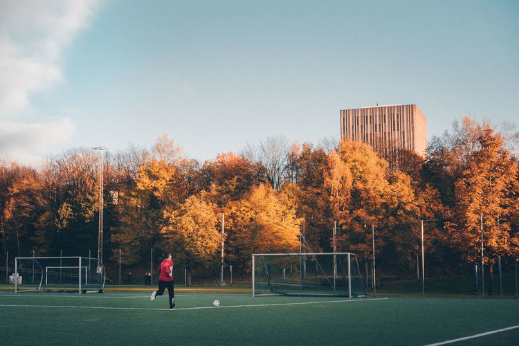 Man playing soccer on field by trees in city sky