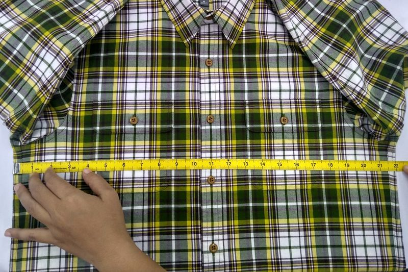 Cropped hand measuring shirt with tape measure