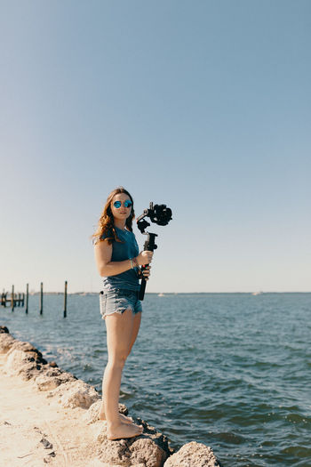 Portrait of young woman photographing sea against clear sky