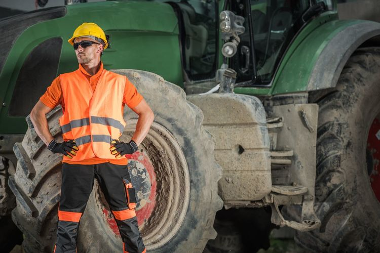 Manual worker standing against construction vehicle