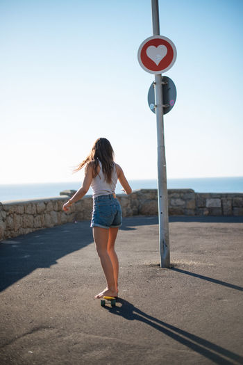 Full length rear view of woman walking on road against sky