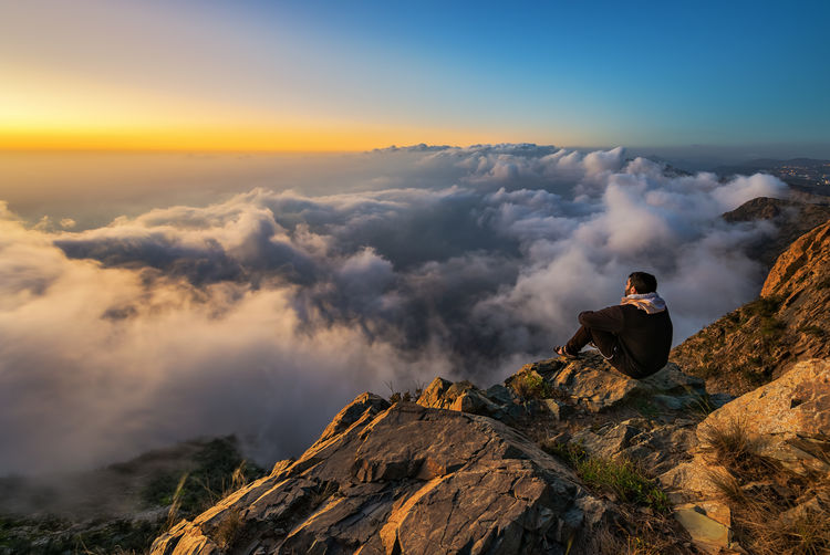 Man sitting on mountain against cloudscape during sunset