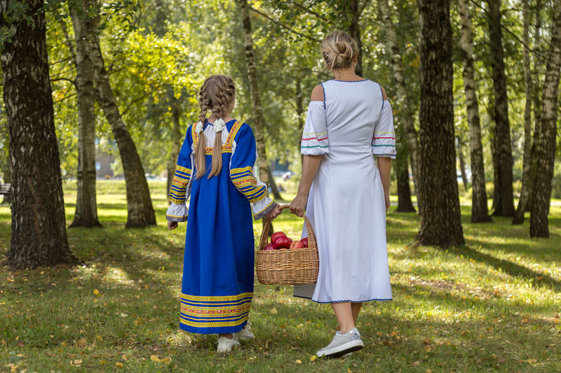 Rear of woman with daughter holding apple basket while walking on field