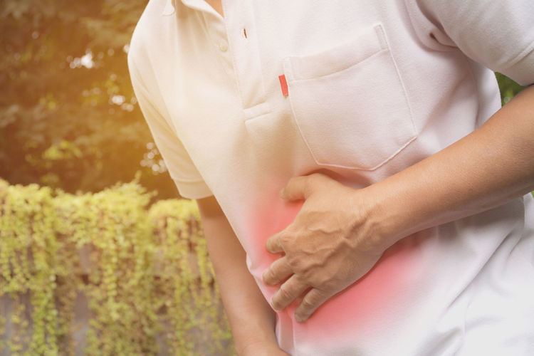 Midsection of man with stomachache standing at park