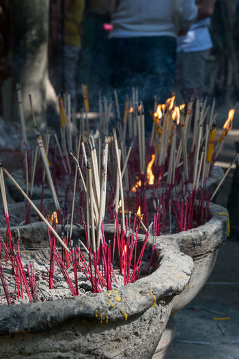 View of burning candles on temple outside building