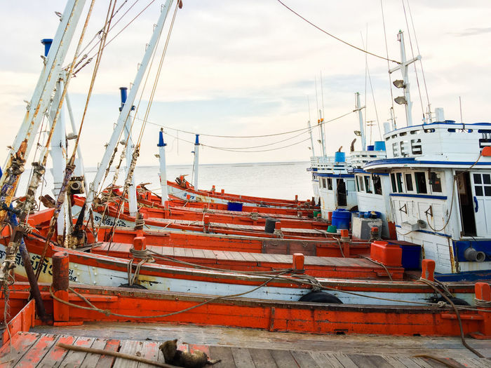 Boats moored at harbor by sea