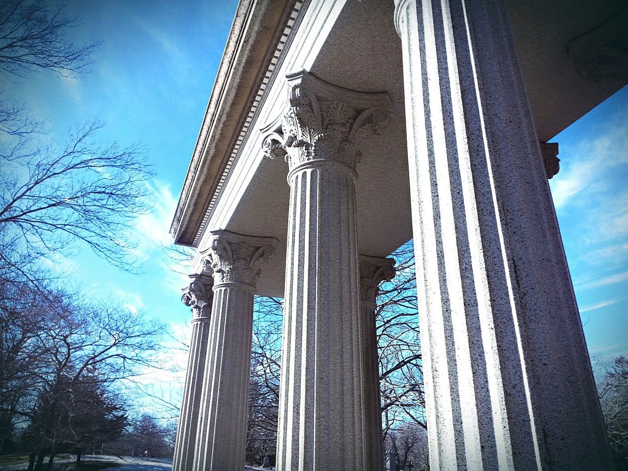 low angle view, architecture, built structure, day, architectural column, sky, no people, outdoors, tree, statue, building exterior, sculpture, nature