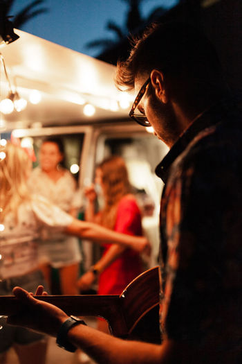 Man playing guitar for friends by illuminated campervan at night