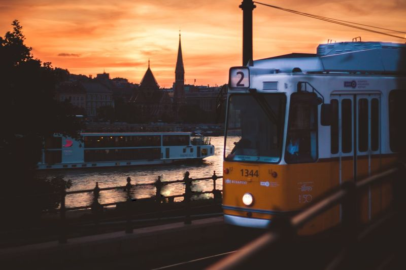 Train in city against sky during sunset
