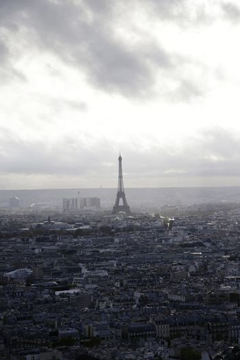Aerial view of city buildings against cloudy sky tour eiffel