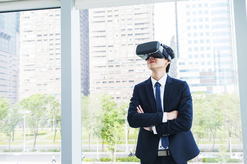 Businessman With Arms Crossed Looking Through Virtual Reality Simulator While Standing By Window In Office