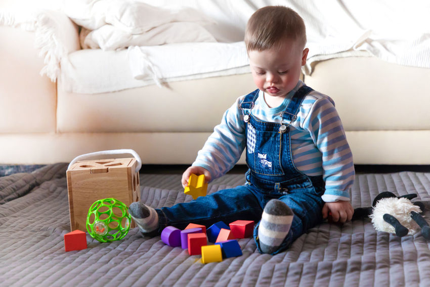 Babyboy Boys Casual Clothing Child Childhood Cute Domestic Room Down Syndrome Flooring Full Length Furniture Home Interior Indoors  Innocence Lifestyles Living Room Mental Health  One Person Playing Real People Sitting Sofa Toy