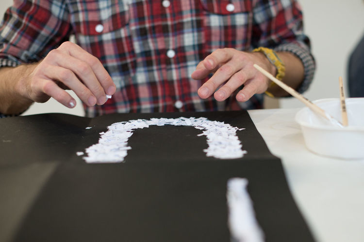 Midsection Of Man Making Text From Paper On Table