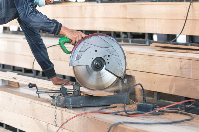 Midsection of man cutting wood in workshop