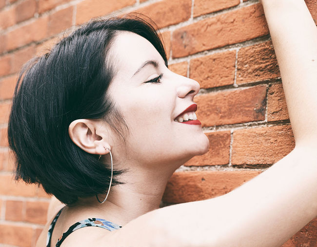 Close-up of smiling woman against wall