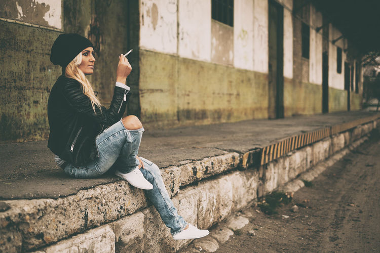 Full length side view of young woman smoking cigarette while sitting against building