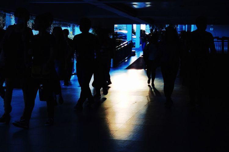 Silhouette people walking in illuminated corridor