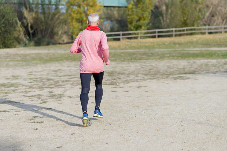 Senior man wearing glasses jogging at the park Adult Adults Only Day Exercising Full Length Healthy Lifestyle Jogging Lifestyles One Person One Woman Only One Young Woman Only Only Women Outdoors People Real People Rear View Sport Sports Clothing Women Young Adult Young Women