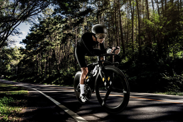 Activity Bicycle Cycling Helmet Day Forest Full Length Headwear Helmet Men Mode Of Transportation Nature One Person Outdoors Plant Real People Riding Road Sport Transportation Tree
