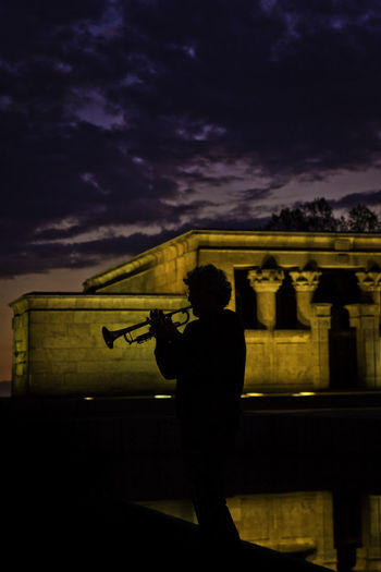 Silhouette Man Playing Trumpet Against Temple Of Debod At Night