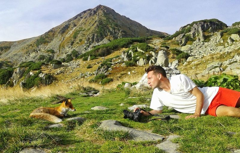 Man photographing with dog on mountain against sky