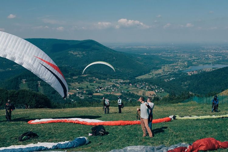 Paragliding Parachute Flying RISK Weekend Fun Paragliding Mountain Cloud - Sky Sky Plant Scenics - Nature Nature Real People Beauty In Nature Landscape Grass Group Of People Environment Leisure Activity Day Sport Mountain Range