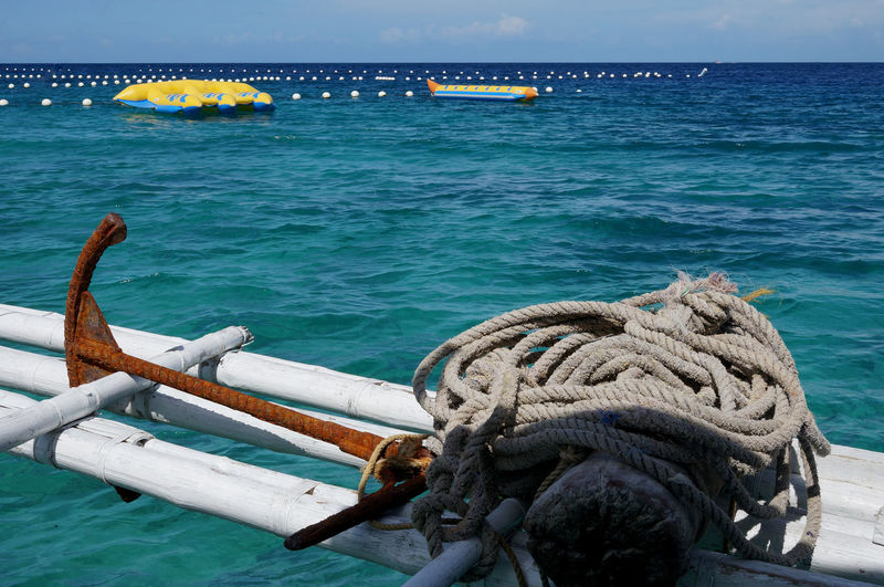 Rusty anchor and rope on bamboos over sea by inflatable rafts against sky