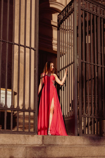 Full Length Of Woman Wearing Red Evening Gown Standing By Metallic Gate