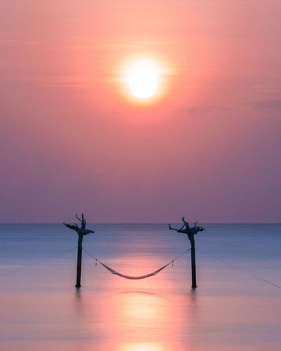 Longexposure Sky Sun Beauty In Nature Scenics - Nature Water Tranquility Silhouette Tranquil Scene Orange Color Sea Nature Reflection No People Idyllic Horizon Over Water Sunlight Fuel And Power Generation Horizon Outdoors